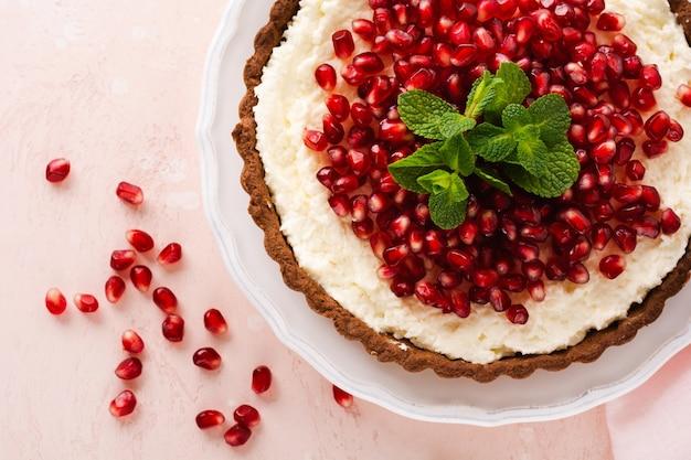 Домашний десертный шоколадный тарт с кокосовым кремом, гранатом и мятой на розовом фоне стола