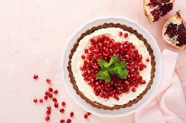 Домашний десертный шоколадный тарт с кокосовым кремом, гранатом и мятой на розовой поверхности стола