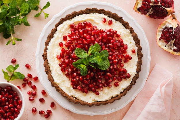 Homemade dessert chocolate tart with coconut cream and pomegranate and mint on a pink table surface. top view