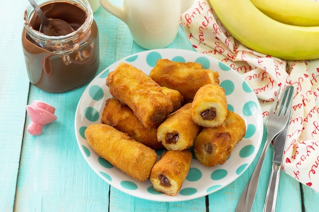 Homemade dessert of fried bananas fried stuffed with chocolate on a wooden table in a rustic style