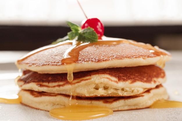 自家製デザート。はちみつと揚げパンケーキ。白いプレートの背景にチェリーとクレープ。伝統的なアメリカ料理。