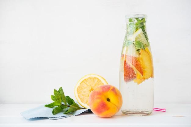 Homemade detox lemonade with lemon and peach in a bottle