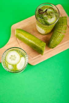 Acqua disintossicante fatta in casa dai cetrioli organici in un bicchiere su uno sfondo verde