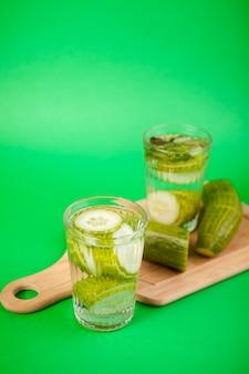 녹색 배경에 유리잔에 담긴 유기농 오이로 만든 홈메이드 디톡스 물