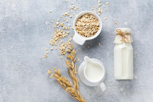 Домашнее диетическое растительное молоко из овсянки на сером фоне. концепция здорового питания. скопируйте пространство и banner.top view.