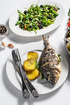 Homemade dinner with baked dorado fish, arugula salad with tomatoes, baked potatoes. white background. top view