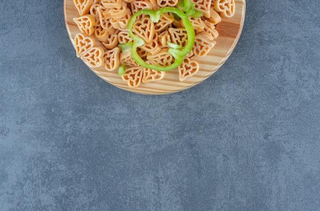 Домашний ужин с макаронами в форме сердца и овощами.
