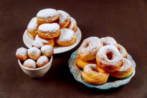 Домашние пончики в белой тарелке, присыпанной сахаром.
