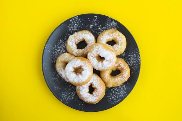Домашние пончики с сахарной пудрой в черной тарелке на желтом