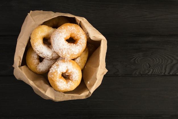 黒い木製の背景の紙のパッケージに粉砂糖を自家製のドーナツ。上面図。