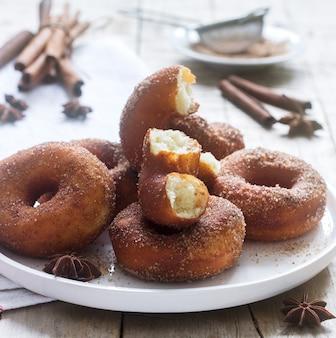 Домашние пончики с сахаром и корицей на деревянном фоне. деревенский стиль