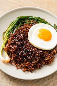 계란후라이와 김치를 곁들인 수제 건조 한국식 매운 블랙 소스 인스턴트 라면