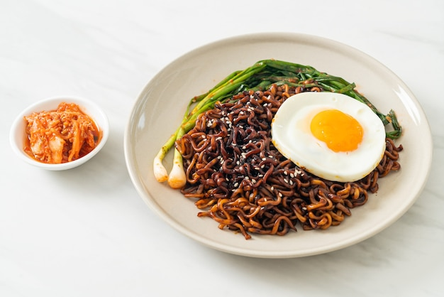 Homemade dried korean spicy black sauce instant noodles with fried egg and kimchi