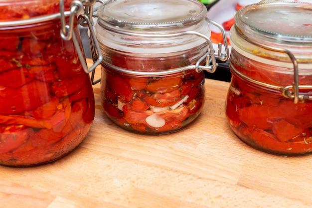Домашние сушеные красные ломтики помидоров со специями базилик и орегано в стеклянной банке. традиционная итальянская средиземноморская кухня.