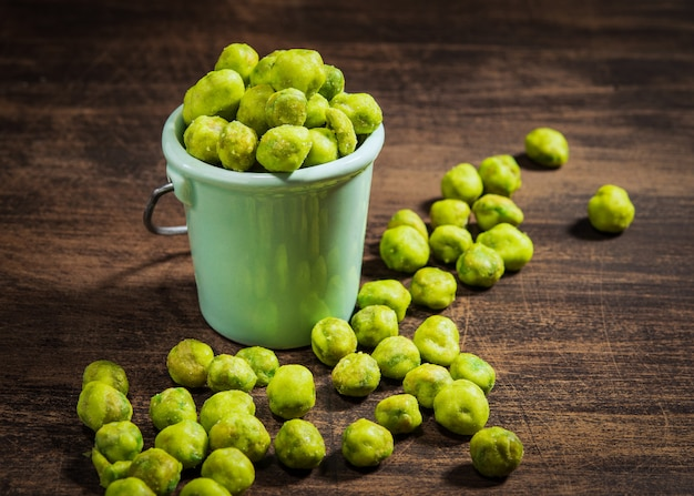 Homemade dry spice wasabi peas as an appetizer on a dark wooden background.