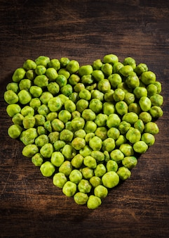 Homemade dry spice wasabi peas as an appetizer in heart shape on wood background.