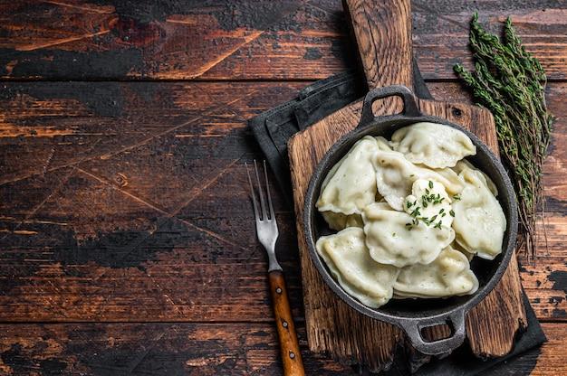 수제 만두, vareniki, pierogi는 냄비에 감자로 채워져 있습니다. 어두운 나무 테이블. 평면도.
