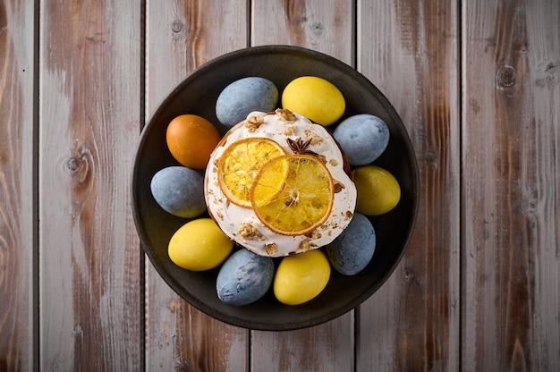 Домашний пасхальный кулич и разноцветные крашеные яйца на черном блюде
