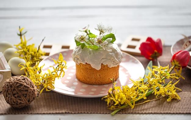 花と装飾の詳細の間でテーブルの上の自家製イースターケーキのクローズアップ。自宅でイースター休暇のコンセプト。