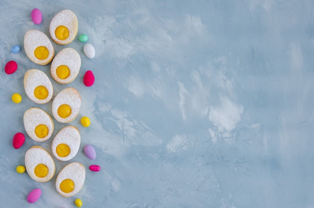 粉砂糖とレモンのクリームが水色のコンクリート背景にイースターエッグの形で自家製イースタークッキー。グリーティングカード。イースターの背景。
