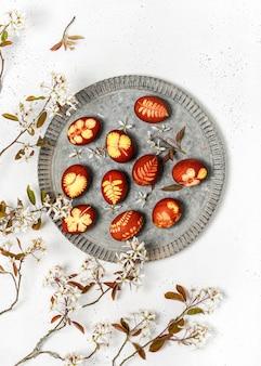 Serviceberry 나무의 야생 흰 꽃과 소박한 금속 접시에 만든 부활절 달걀.