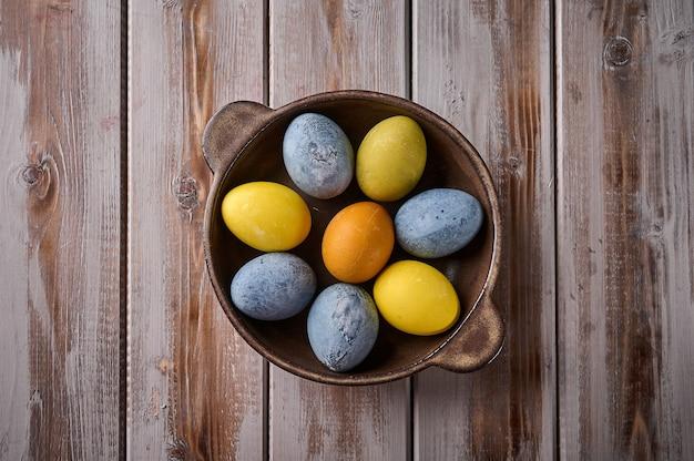 Самодельные пасхальные разноцветные крашеные яйца на керамическом блюде