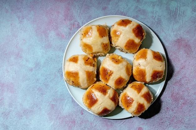 파란색 질감 표면 위에 세라믹 접시에 만든 부활절 전통적인 뜨거운 십자가 빵