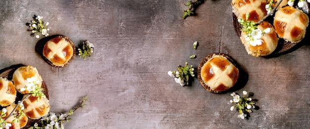 갈색 질감 테이블 위에 꽃 벚꽃 가지와 세라믹 접시에 만든 부활절 전통적인 뜨거운 십자가 빵. 플랫 레이, 공간