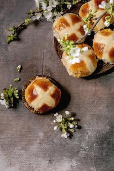 꽃 벚꽃 가지와 세라믹 접시에 만든 부활절 전통적인 뜨거운 십자가 빵
