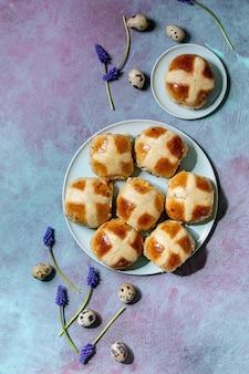 Muscari 꽃, 메추라기 계란, 파란색 질감 표면에 섬유와 세라믹 접시에 만든 부활절 전통적인 뜨거운 십자가 빵