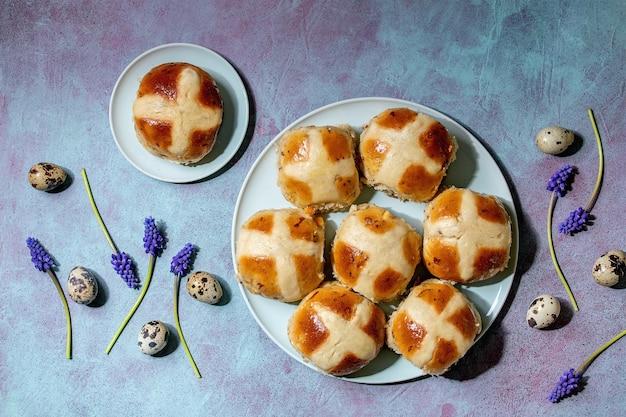 Muscari 꽃, 메추라기 계란, 파란색 텍스처 테이블 위에 섬유와 세라믹 접시에 만든 부활절 전통적인 뜨거운 십자가 빵. 플랫 레이, 공간