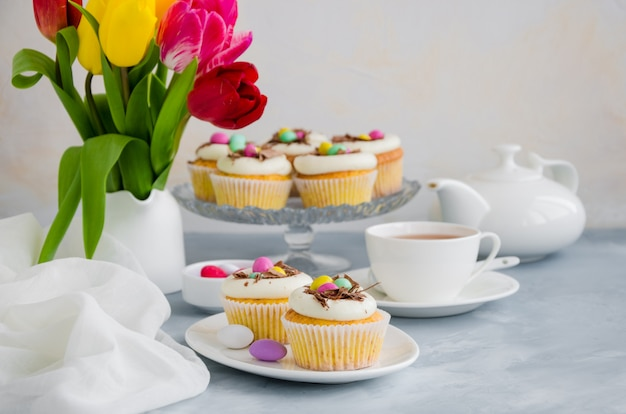Homemade easter vanilla cupcakes bird's nest with butter cream, chocolate and candy eggs on a dish. easter fun food idea for kids.