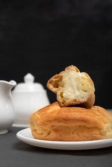Домашний эклер нарезанный с начинкой внутри. сладкая выпечка, крупный план. выпечка к чаю. вертикальная рамка.