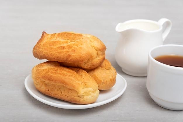 Домашние эклеры и чай с молоком. традиционные французские эклеры. профитроли на белом блюдце.