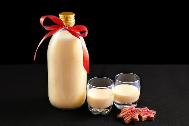 ボトルに入った自家製エッグノッグと暗い背景にクリスマスクッキーとグラス2杯