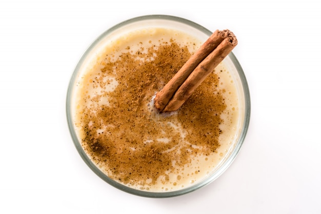 Homemade eggnog with cinnamon in glass isolated on white, typical christmas dessert