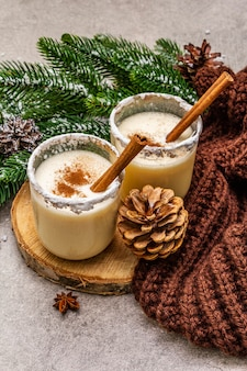 Homemade eggnog with cinnamon in glass. typical christmas dessert. evergreen fir brunch, cones, cozy plaid, artificial snow.