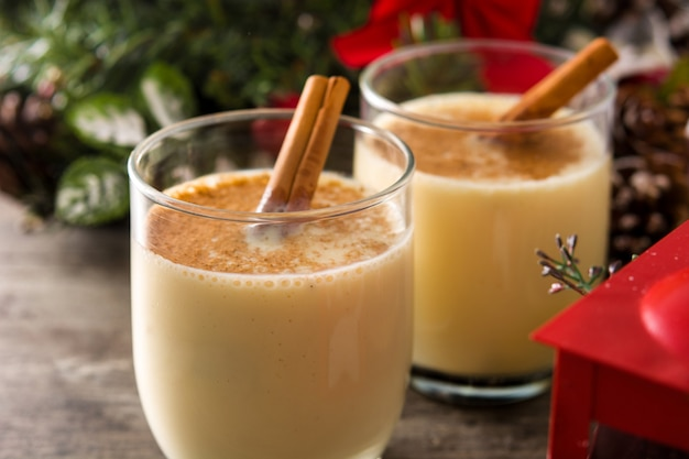 Homemade eggnog with cinnamon in glass on wooden table, typical christmas dessert.