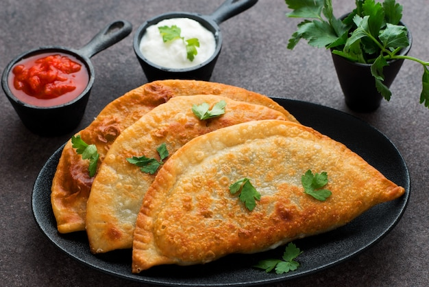 Homemade empanadas with filling and tomato sauce
