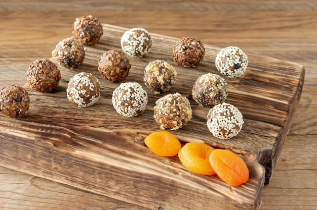 木製の背景にドライアプリコット、レーズン、ナツメヤシ、プルーン、クルミ、アーモンド、ココナッツを使った自家製エナジーボール。健康的な甘い食べ物。