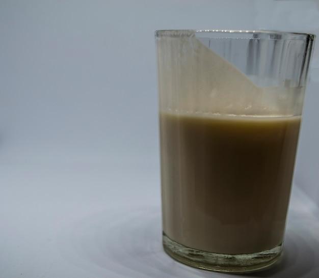 흰색 배경에 있는 유리 케피어 코티지 치즈에 담긴 홈메이드 발효 음료