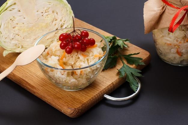 유리 그릇에 당근과 가막살나무 클러스터를 넣은 홈메이드 발효 양배추. 배경에 양배추와 유리 항아리의 신선한 머리. 비건 샐러드. 요리는 비타민 u가 풍부합니다. 건강에 좋은 음식입니다.