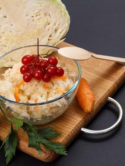 당근, 유리 그릇에 viburnum 클러스터 및 나무 숟가락으로 만든 수제 발효 양배추