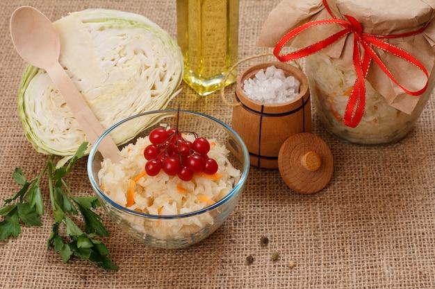 유리 그릇과 항아리에 당근을 넣은 홈메이드 발효 양배추, 자루천에 신선한 양배추 머리, 소금, 기름 한 병. 비건 샐러드. 요리는 비타민 u가 풍부합니다. 건강에 좋은 음식입니다.
