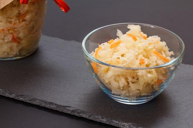 검은 배경에 유리 그릇에 당근과 항아리를 넣은 홈메이드 발효 양배추. 비건 샐러드. 요리는 비타민 u가 풍부합니다. 건강에 좋은 음식입니다.
