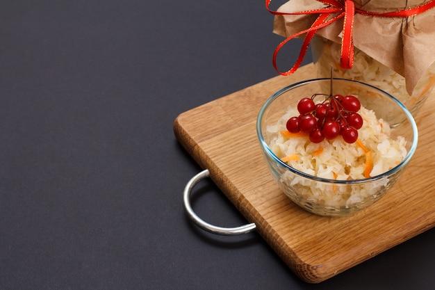 유리 그릇에 당근을 넣은 홈메이드 발효 양배추는 배경에 가막살나무와 유리병 클러스터로 장식되어 있습니다. 비건 샐러드. 요리는 비타민 u가 풍부합니다. 건강에 좋은 음식입니다.