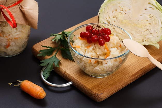 가막살 나무속으로 장식된 유리 그릇에 당근을 넣은 홈메이드 발효 양배추. 배경에 양배추와 유리 항아리의 신선한 머리. 비건 샐러드. 접시에는 비타민 u가 풍부합니다.