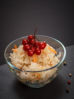 검은 배경에 가막살나무 덩어리로 장식된 유리 그릇에 당근을 넣은 홈메이드 발효 양배추. 비건 샐러드. 요리는 비타민 u가 풍부합니다. 건강에 좋은 음식입니다.