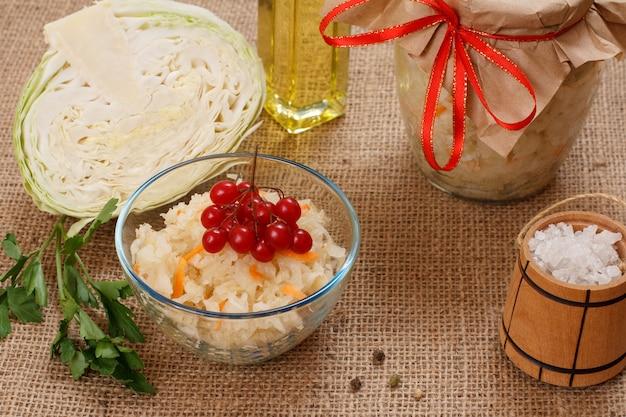 유리 그릇에 당근을 넣은 홈메이드 발효 양배추, 신선한 양배추 머리, 소금, 유리병, 그리고 자루천에 기름 한 병. 비건 샐러드. 요리는 비타민 u가 풍부합니다. 건강에 좋은 음식입니다.