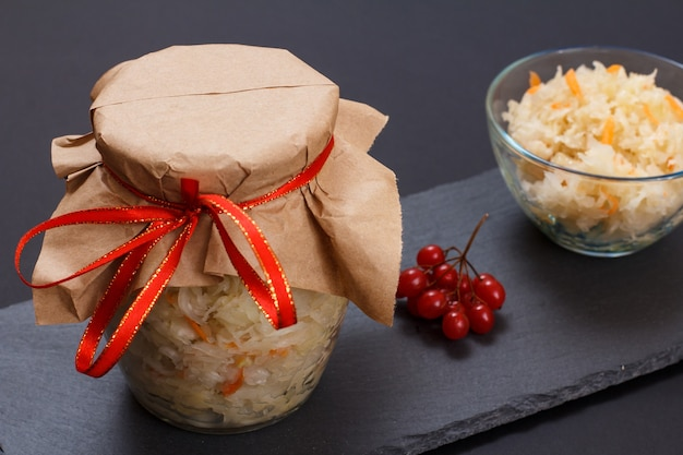 유리병과 그릇에 당근을 넣은 홈메이드 발효 양배추, 배경에 가막살나무 클러스터. 비건 샐러드. 요리는 비타민 u가 풍부합니다. 건강에 좋은 음식입니다.